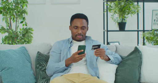 African man holding debit card and using smartphone for shopping at home. Online Live Action