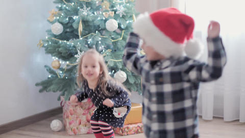 3 authentic happy Joy children wave hands hello rejoice by Christmas tree play Live Action