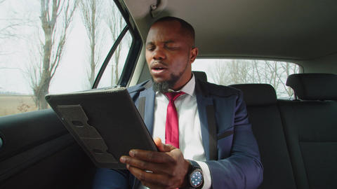 Busy black entrepreneur talking on video chat in vehicle Live Action