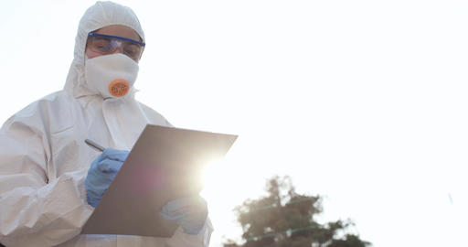 Female Doctor Wearing a Facemask and Suit Stands Outside in the Sunset. Nurse Live Action