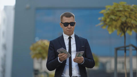 Rich man in stylish suit wearing sunglasses counting money and walking near Live Action