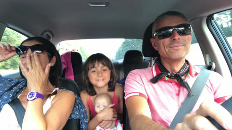 Happy family singing in the car while traveling. Holiday and travel concept Live Action
