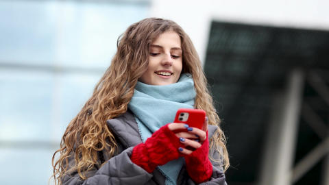 Curly-haired female using smartphone standing outside. A smiling happy girl Live Action