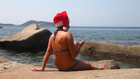 Woman on the beach in santa hat calls on the phone Footage