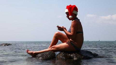 Woman on the beach in santa hat calls on the phone Stock Video Footage