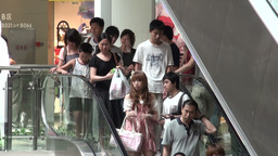 Shoppers using escalators in a mall in Guangzhou Footage