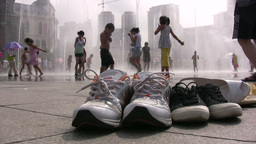 Children play with a water fountain, their shoes s Stock Video Footage