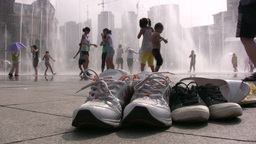 Children play with a water fountain, their shoes s Footage