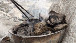 Poking burning manure near a traditional yurt Stock Video Footage