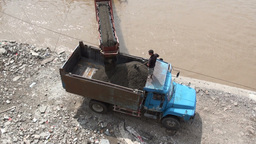 Unloading sand from a boat into a truck using a co Stock Video Footage