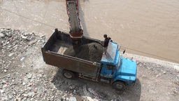 Unloading sand from a boat into a truck using a co Footage