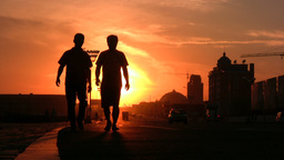 Two Chinese men walk through a street at a beautif Footage