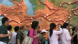 Chinese tourists walk past Iran map Stock Video Footage