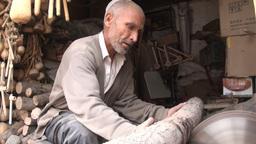 Old Uyghur man cuts large chunks of wood Stock Video Footage