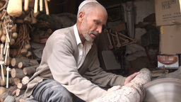 Old Uyghur man cuts large chunks of wood Footage