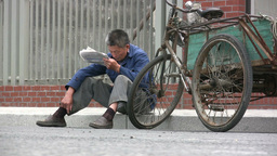 Man reading newspaper in China Stock Video Footage