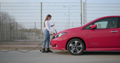 Girl at the charging station for electric vehicles inserts a plug into the car Live Action