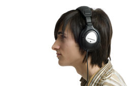 Young man listening to music with headphones on white background フォト