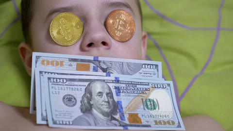 Rich Teen Boy Lies, on a Bed with Dollars, Gold Bitcoins on Eyes. Humor. 4K Live Action