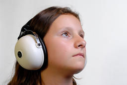 Young girl looking up and listening to music on large headphones ภาพถ่าย