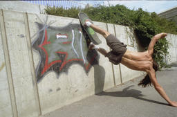 Skateboarder makes a jump against the wall ภาพถ่าย