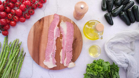 hand putting raw fed bacon strips on chopping board Live Action