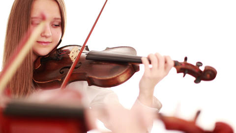 Two teenager playing the violin, studio shot Live Action