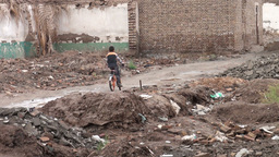Boy cycles through demolished Kashgar old town Stock Video Footage