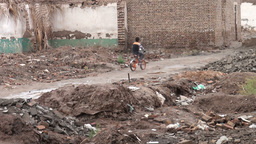 Boy Cycles Through Demolished Kashgar Old Town stock footage