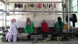 Girls discussing carpet work in Chinese factory Stock Video Footage