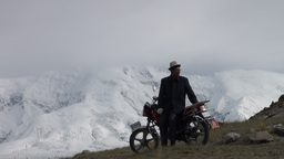 Kyrgyz man greets friends at motorbike before moun Footage