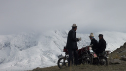 Kyrgyz man greets friends at motorbike before moun Stock Video Footage