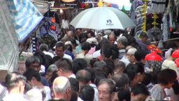 Person holds umbrella high at busy Kowloon market, Footage