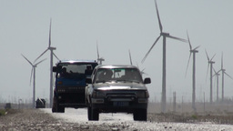 Truck and jeep drive in front of Chinese windmill  Footage