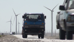 Truck and jeep drive in front of Chinese windmill Stock Video Footage