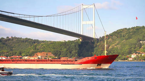 Red cargo ship sailing under Bosporus Bridge Footage