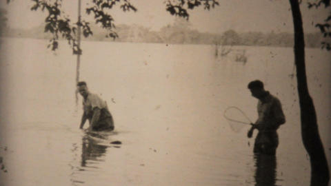 Two Men Try To Catch Fish In Flooded Backyard In Dallas 1948 Vintage 8mm Footage