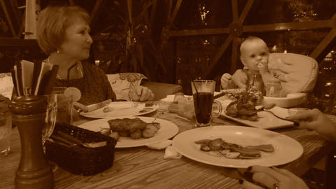 Family in restaurant, old style sepia view with grain Footage