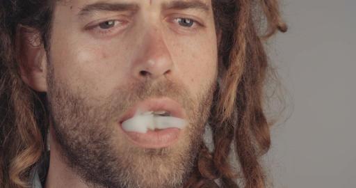 Man with dreadlocks smoking a joint of medicinal marijuana Live Action