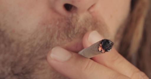 Man with dreadlocks smoking a joint of medicinal marijuana Footage