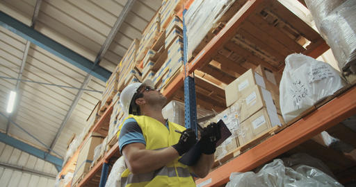 Man wearing a helmet working in a large industrial warehouse Footage