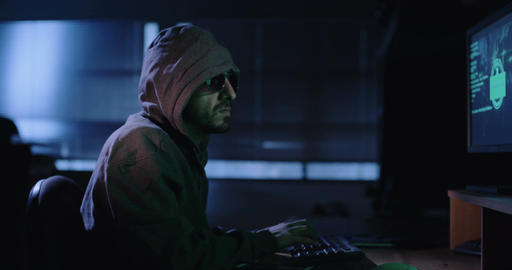 Computer hacker sitting in a dark room hacking computers Live Action