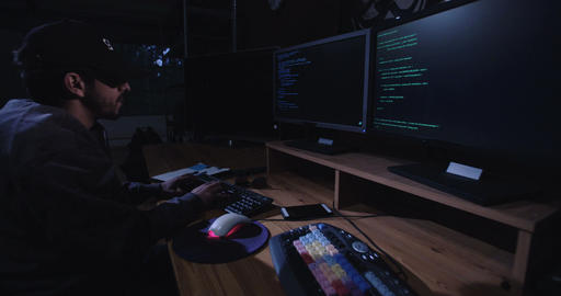 Hacker sitting in a dark room hacking remote computers Live Action
