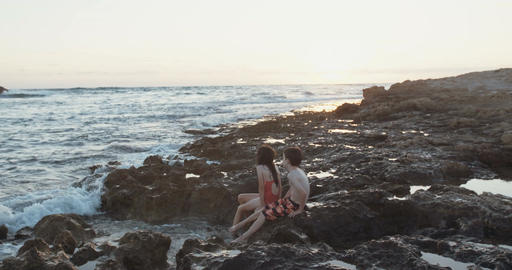 Two kids sitting on the beach looking towards the sunset Footage