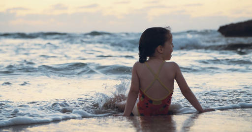 Little girl at the beach during sunset, playing with the waves Live Action