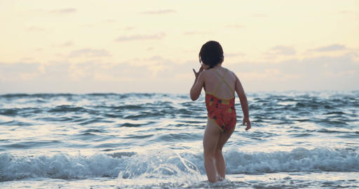 Little girl at the beach during sunset, playing with the waves Footage