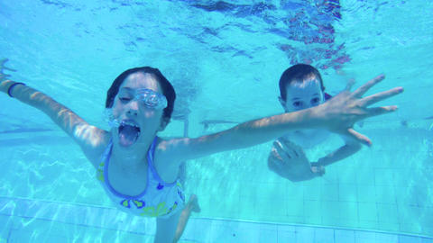 Underwater footage of two children jumping and diving in a swimming pool ビデオ