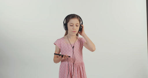 Girl listening to music from a mobile phone with earphones and dancing 画像