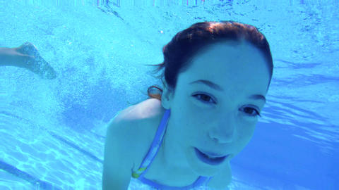Underwater footage of two children jumping and diving in a swimming pool Footage