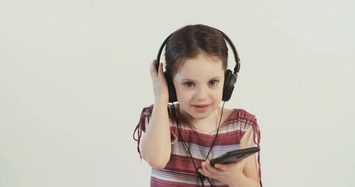 Little girl listening to music from a mobile phone with earphones and dancing Live Action